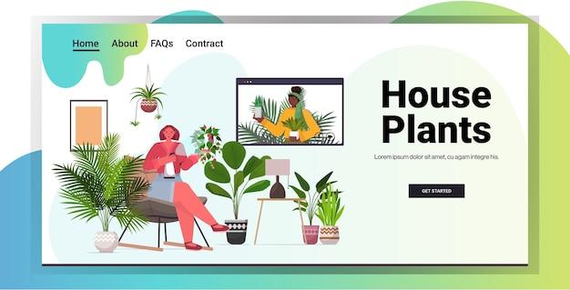 Mescolare donne di razza che si prendono cura di ragazze di piante d'appartamento che hanno riunione virtuale durante la videochiamata soggiorno interno copia spazio orizzontale