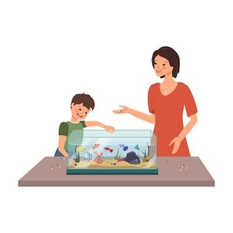 Mamma e ragazzo danno da mangiare ai pesci nell'acquario