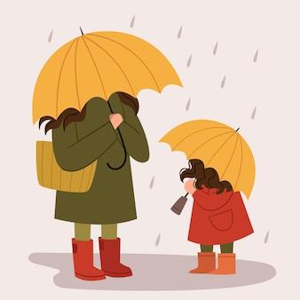 Mamma e figlia con gli ombrelli gialli camminano sotto la pioggia. passeggiata autunnale. giorno della famiglia.