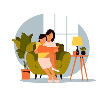 Mamma che legge per la figlia che si siede sul divano con il libro.