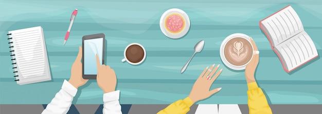 Moody piatto laici sfondo con posto di lavoro in un bar. le mani delle donne che tengono una tazza di cappuccino e mangiano il bigné. sfondo in legno azzurro con libro, taccuino. un uomo in possesso di uno smartphone.