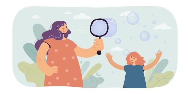 Madre e figlia che gonfiano bolle d'aria. donna e ragazza che giocano insieme, tempo felice in famiglia insieme.