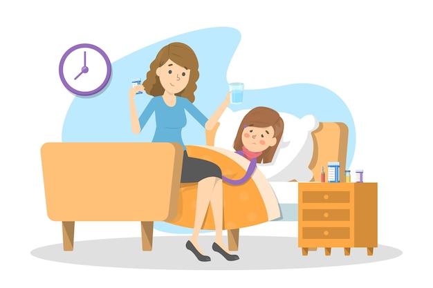 La madre dà le pillole a un bambino malato con la febbre