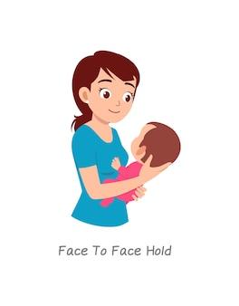 Madre che tiene in braccio il bambino con una posa chiamata presa faccia a faccia