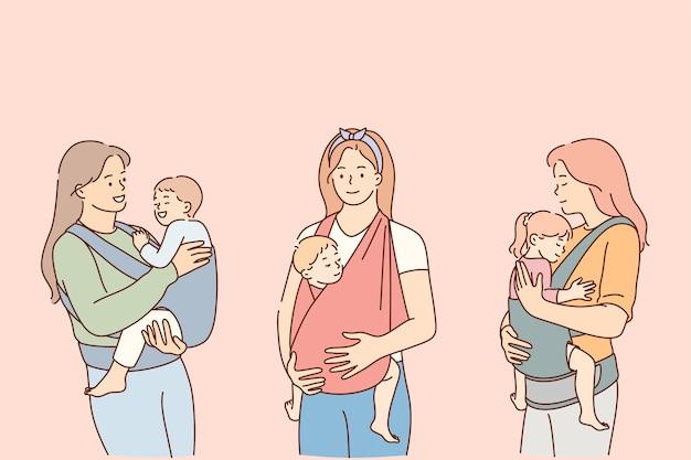 Madri che trasportano i loro bambini nel concetto di stile di vita delle imbracature.