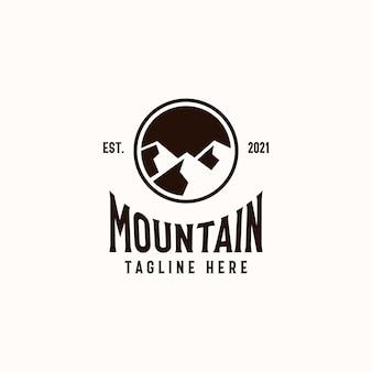 Modello di logo distintivo di montagna isolato in sfondo bianco