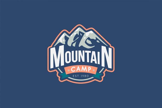 Modello di logo del campo di montagna. illustrazione di rocce con la tipografia. distintivo retrò di alpinismo
