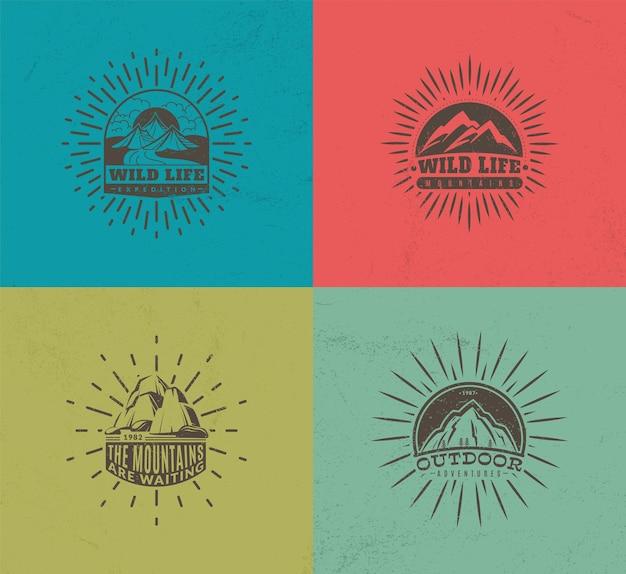 Emblemi di montagna. set di quattro distintivi vintage colorati vettoriali, campo di alpinismo e turismo d'avventura, etichette retrò per spedizioni escursionistiche, raccolta di illustrazioni vettoriali monocromatiche isolate