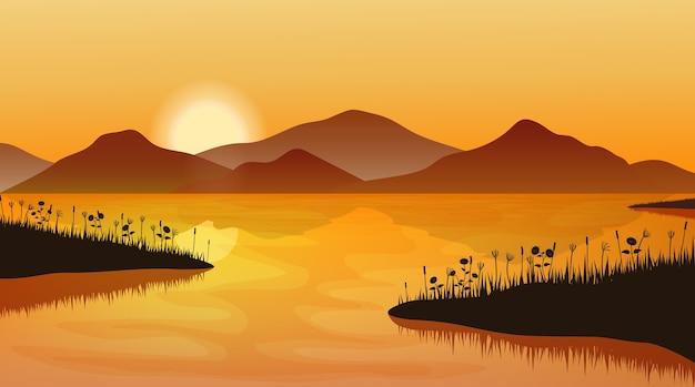 Paesaggio di montagna al tramonto. sagoma di erba sopra l'acqua e la catena montuosa.