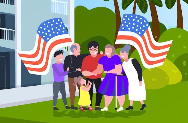 Famiglia multi-generazione che tiene le bandiere degli stati uniti che celebrano, celebrazione del giorno dell'indipendenza americana del 4 luglio.