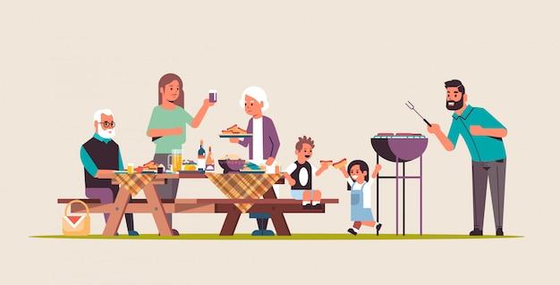 Famiglia multi generazione che prepara hot dog sulla griglia genitori e bambini dei nonni divertendosi picnic barbecue concetto piatto orizzontale a figura intera