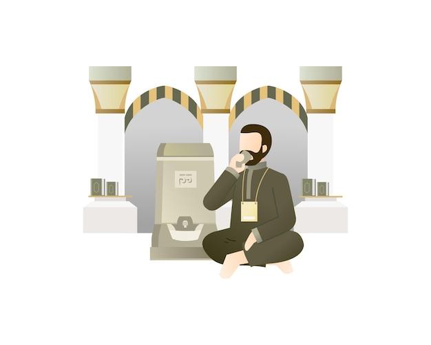 Uomo musulmano che beve acqua di zamzam