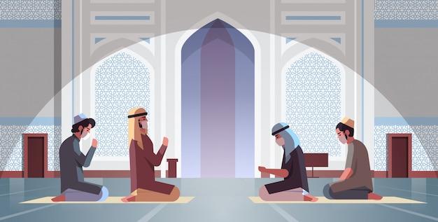 Uomini musulmani in maschere che pregano il ramadan kareem mese santo religione coronavirus quarantena pandemica