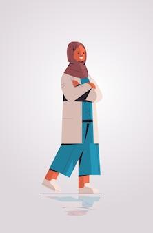 Donna musulmana medico in uniforme arabo femmina professionista medico posa permanente medicina concetto sanitario illustrazione vettoriale verticale a figura intera