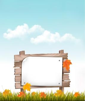 Sfondo della natura con foglie di autunno e cartello in legno
