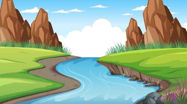 Paesaggio della foresta naturale nella scena diurna con un lungo fiume che scorre attraverso il prato