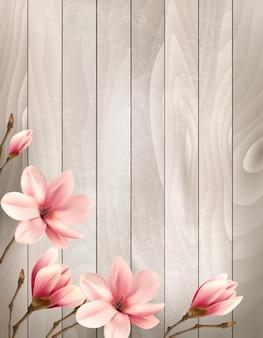 Sfondo di primavera natura con rami di magnolia bella sul cartello in legno. Vettore Premium