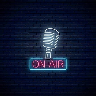 Segno al neon sull'aria con microfono retrò sul fondo del muro di mattoni scuri. insegna luminosa della stazione radio. icona del caffè sonoro. manifesto dello spettacolo musicale. illustrazione vettoriale.