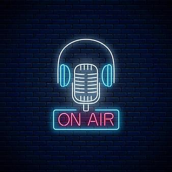 Segno al neon in aria con microfono retrò e cuffie sul fondo del muro di mattoni scuri. insegna luminosa della stazione radio.