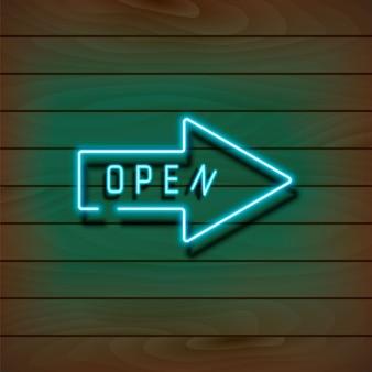 Freccia blu al neon aperta su una parete di legno