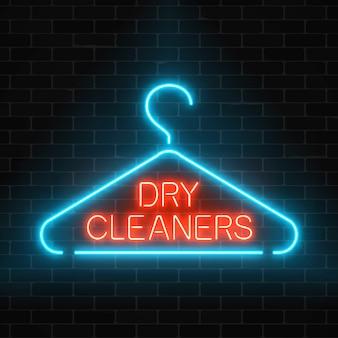 Segno d'ardore delle lavanderie a secco al neon con il gancio su un fondo scuro del muro di mattoni.
