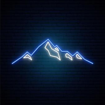 Icona delle montagne al neon sullo sfondo del muro di mattoni scuri