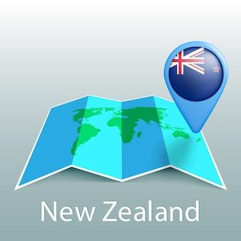 Mappa del mondo di bandiera della nuova zelanda nel pin con il nome del paese su sfondo grigio
