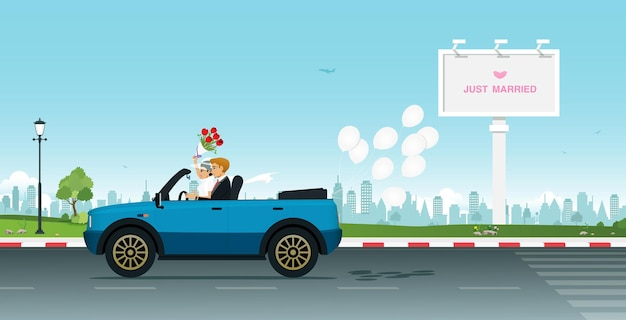 Una coppia di sposi che guida su una strada cittadina con cartelloni pubblicitari.