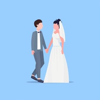 Sposi uomo donna in piedi insieme coppia romantica sposi per mano giorno delle nozze celebrazione concetto maschio femmina personaggio dei cartoni animati a figura intera