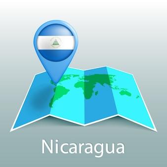 Mappa del mondo di bandiera del nicaragua nel perno con il nome del paese su sfondo grigio