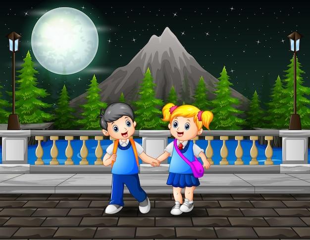 Paesaggio notturno con i bambini delle scuole di ritorno a casa