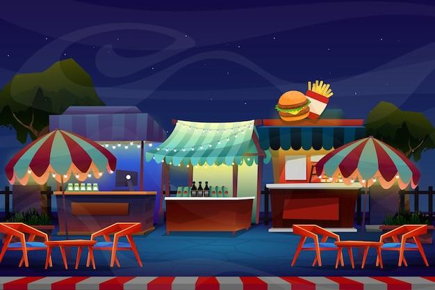 Scena notturna di mini cabina o negozio di bevande con sedia e tavolo sotto ombrellone o ombrellone vicino al parco naturale