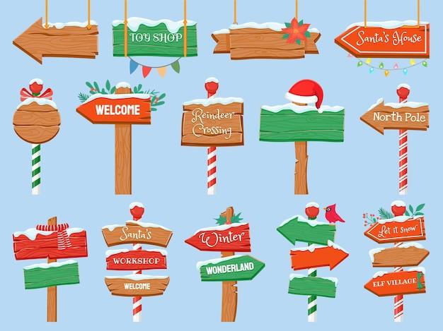 Segni del polo nord. cartello stradale in legno di natale con neve. direzione del cartello della freccia per l'officina di babbo natale. insieme di vettore del negozio di giocattoli per le vacanze invernali
