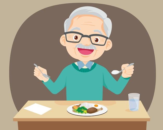 Il vecchio uomo anziano felice mangia cibo