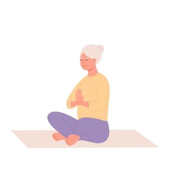 Vecchia donna che si rilassa allo yoga stile di vita sano una donna anziana si siede nella posizione del loto e medita