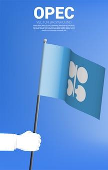 Bandiera dell'opec in mano dell'uomo d'affari. sfondo per l'industria petrolifera e petrolchimica.