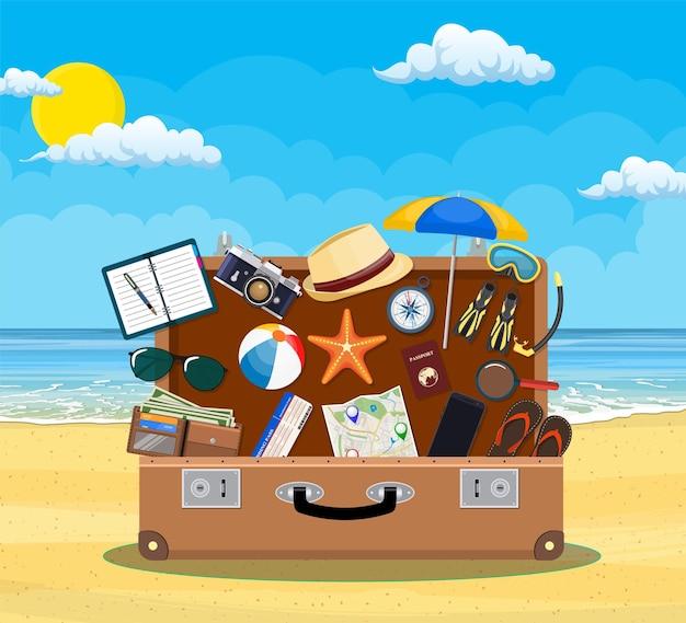 Bagagli aperti, bagagli, valigie con icone di viaggio e oggetti in spiaggia