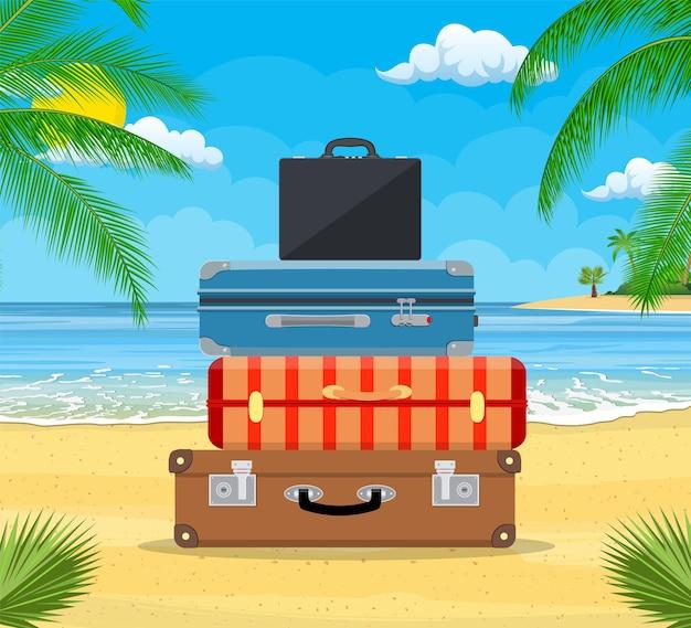 Bagaglio aperto, bagagli, valigie con icone di viaggio e oggetti sulla spiaggia tropicale