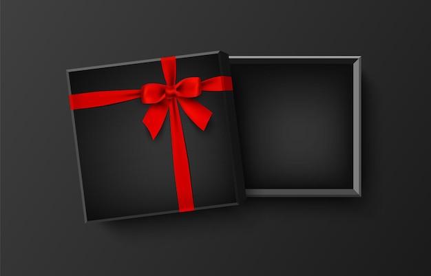 Contenitore di regalo vuoto nero aperto con fiocco rosso e nastro