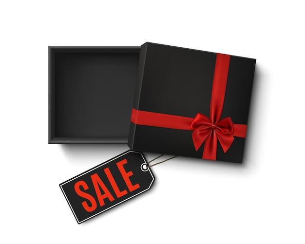 Contenitore di regalo vuoto nero aperto con nastro rosso, fiocco e cartellino del prezzo di vendita su priorità bassa bianca. vista dall'alto. modello per banner, brochure o poster. illustrazione.