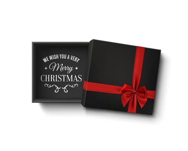 Contenitore di regalo vuoto nero aperto con nastro rosso e fiocco