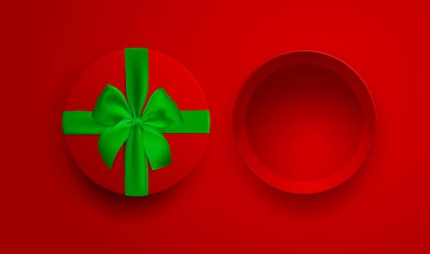 Scatola regalo vuota rossa aperta con nastro verde e fiocco isolato su sfondo rosso vista dall'alto