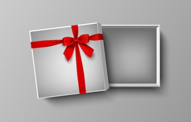Contenitore di regalo vuoto bianco aperto con fiocco rosso e nastro