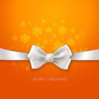 Biglietto di auguri di natale arancione con nastro con fiocco in seta bianca