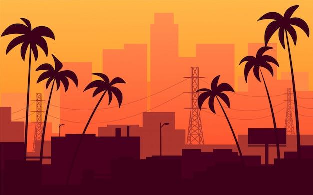 Tramonto arancio in california, vista della città con le palme.