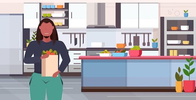 Uomo in sovrappeso che tiene la spesa shopping bag dieta dieta concetto di perdita di peso ragazzo con verdure e frutta alimenti biologici cucina moderna ritratto interno piano orizzontale