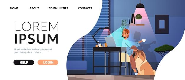 Oberato di lavoro donna d'affari freelance guardando lo schermo del computer portatile donna seduta sul posto di lavoro vicino al cane nella notte buia stanza di casa orizzontale a figura intera spazio copia