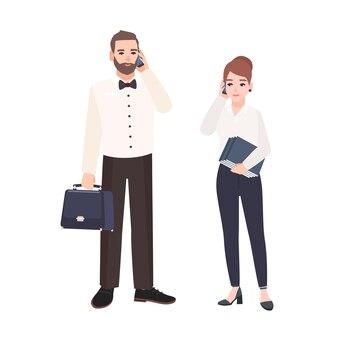 Coppia di impiegati vestiti in abiti d'affari in piedi e parlando al telefono.
