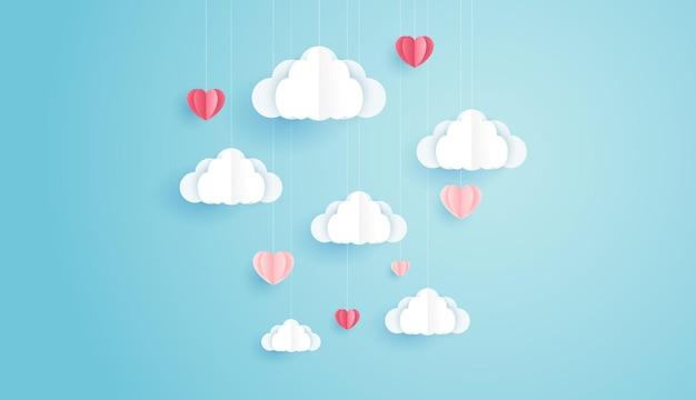L'arte cartacea dell'amore e il giorno di san valentino con cuore di carta e nuvole galleggiano sul cielo blu possono essere