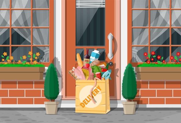 Sacchetto di carta di generi alimentari lasciato alla porta della casa vivente. consegna del cibo da negozio, bar, ristorante. consegna espressa di prodotti alimentari. pane, carne, latte, frutta verdura, bevande. illustrazione vettoriale piatta